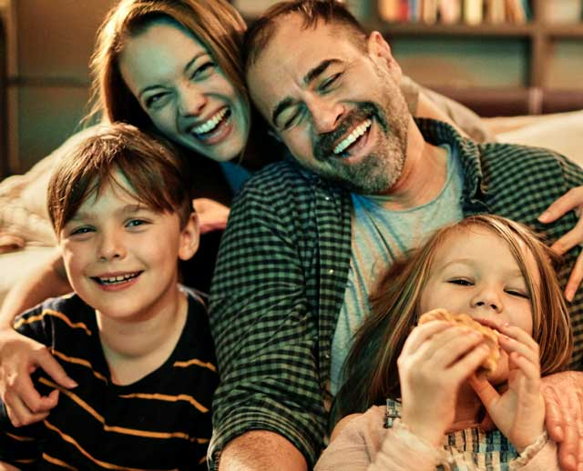A family hugs while laughing together after learning how a whole life insurance policy can keep their family protected