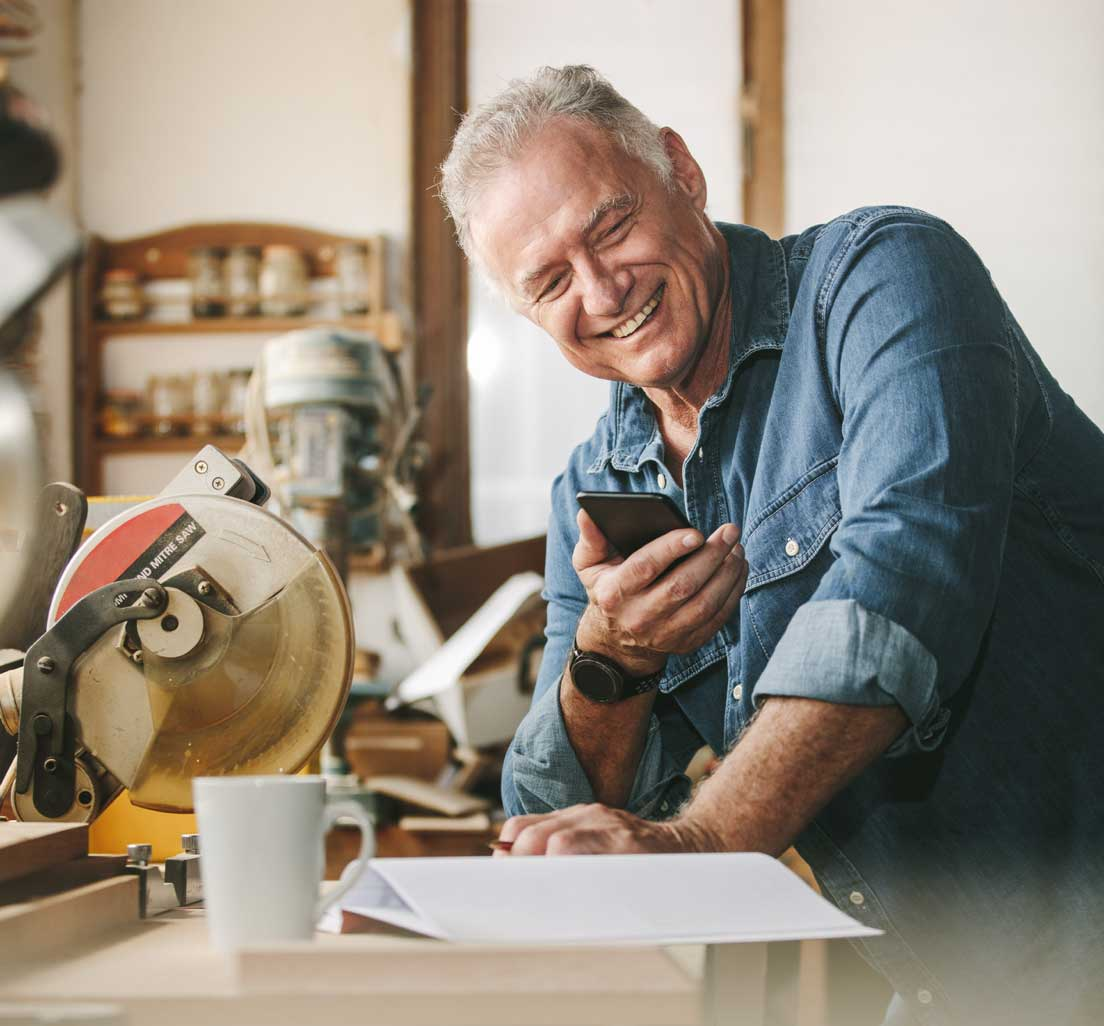 An older man in his workshop is happy to receive his term life insurance quote from SelectQuote
